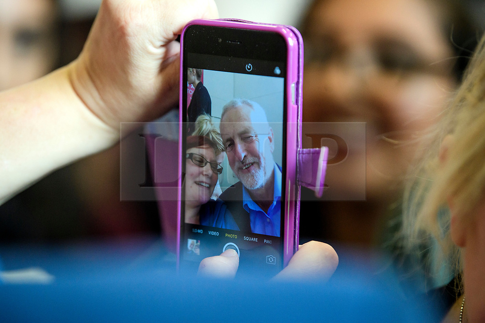 © Licensed to London News Pictures. 07/08/2017. Crawley, UK. Labour Party leader JEREMY COBYN seen on a mobile phone as he poses for a selfie while being greeted by supporters and party members at a campaign visit in Crawley, Surrey. Corbyn has faced recent criticisms for his response to the crisis in Venezuela, a country ruled by a government he has openly backed in the past.  Photo credit: Ben Cawthra/LNP