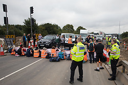 Enfield, UK. 15th September, 2021. Metropolitan Police officers monitor Insulate Britain climate activists blocking a slip road from the M25 at Junction 25 as part of a campaign intended to push the UK government to make significant legislative change to start lowering emissions. The activists, who wrote to Prime Minister Boris Johnson on 13th August, are demanding that the government immediately promises both to fully fund and ensure the insulation of all social housing in Britain by 2025 and to produce within four months a legally binding national plan to fully fund and ensure the full low-energy and low-carbon whole-house retrofit, with no externalised costs, of all homes in Britain by 2030 as part of a just transition to full decarbonisation of all parts of society and the economy.