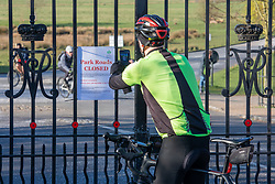 © Licensed to London News Pictures. 23/03/2020. London, UK. A cyclist takes a picture of a sign saying Park Roads Closed which has been posted on the gates of Roehampton Gate, Richmond Park this morning. Royal Parks have temporarily banned all cars from entering Richmond Park, Bushy Park and Greenwich Park after a huge surge in traffic on Saturday and Sunday with large numbers of people ignoring the social distancing guidelines. Cyclists and walkers can continue to enter the parks as the coronavirus crisis continues. Photo credit: Alex Lentati/LNP