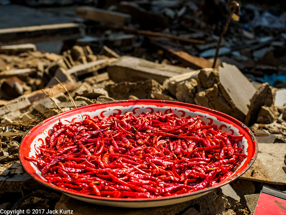 28 MARCH 2017 - BANGKOK, THAILAND: A tray of red chilies dries in the sun in the rubble of a destroyed home in Pom Mahakan. The final evictions of the remaining families in Pom Mahakan, a slum community in a 19th century fort in Bangkok, have started. City officials are moving the residents out of the fort. NGOs and historic preservation organizations protested the city's action but city officials did not relent and started evicting the remaining families in early March.                  PHOTO BY JACK KURTZ