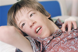 Portrait of young boy with Cerebral Palsy; who is waiting for a Baclofen Implant pump operation; lying on hospital bed on Children's ward,