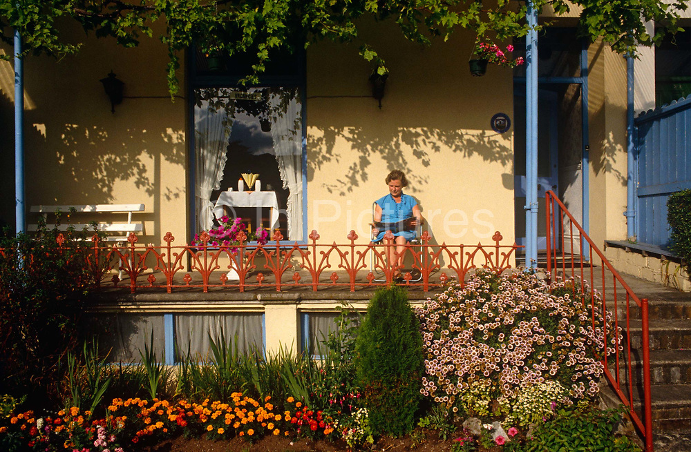 It is late morning and a lady has emerged from her bead and breakfast (B+B)  in Paignton, Devon. Sunlight is quite high in the sky and the shadows of a vine that is growing across the roof of the building's terrace, is seen on the wall behind the woman. She is seated reading a magazine in a garden chair and is surrounded by colourful flowers in their prime. Well-painted original victorian railings that act as a sort of ballustrade are in front of the female. In the window is a scene of typical seaside Englishness. Serviettes are splayed out on a table along with breakfast or dinner items awaiting guests at the next meal.