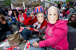 Plymouth, UK  29/04/2011. The Royal Wedding of HRH Prince William to Kate Middleton. Residents of Plymouth wear face masks of the Queen and Phillip whilst watching the royal wedding unfold. Photo credit should read London News Pictures.