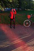 Red-tinted landscape with lady wearing red caused by the Serpentine Gallery's Pavillion.