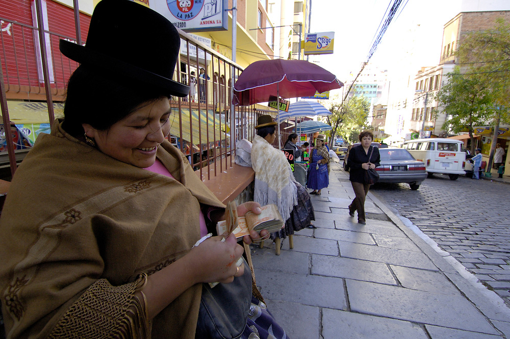 An Aymara indigenous woman changes dollars into Bolivian currency on a street in La Paz, the Andean nation's capital.