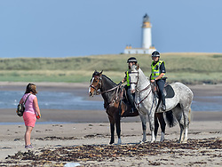 Pictured: Police, including mounted officers, were out in force around the hotel, including on Turnery beach, where they outnumbered protestors, with Turnery lighthouse in the background.<br /> <br /> Protesters gathered amid tight security at the Trump Turnberry resort, where President Trump and his wife Melania are staying on their trip to Scotland.<br /> <br /> © Dave Johnston / EEm