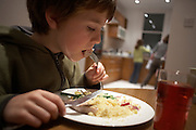 A young 10 year-old boy enjoys a fresh Maldives line caught yellow fin tuna steak, grilled in his London home on a Friday night
