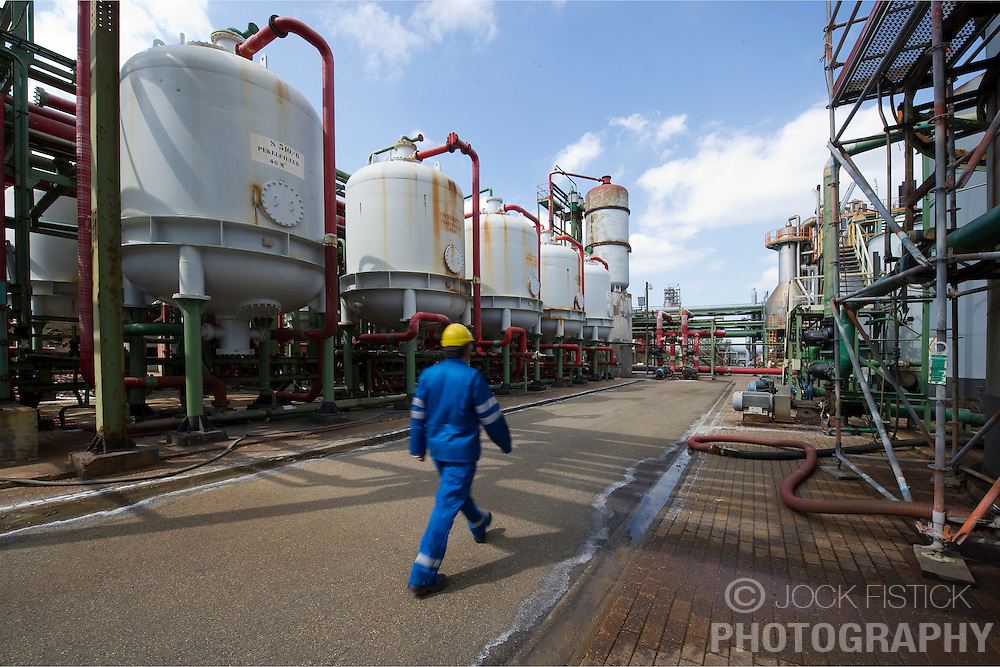 An employee walks past chlorine filtration tanks at the Solvay SA chemical plant in Antwerp, Belgium, on Thursday, April 22, 2010. Chlorine is the main product produced at Solvay's Antwerp facility.  Solvay SA is the world's largest supplier of Soda Ash or Sodium Carbonate and is also a major producer of caustic soda, hydrogen peroxide, chlorine and fluorinated products. (Photo © Jock Fistick)