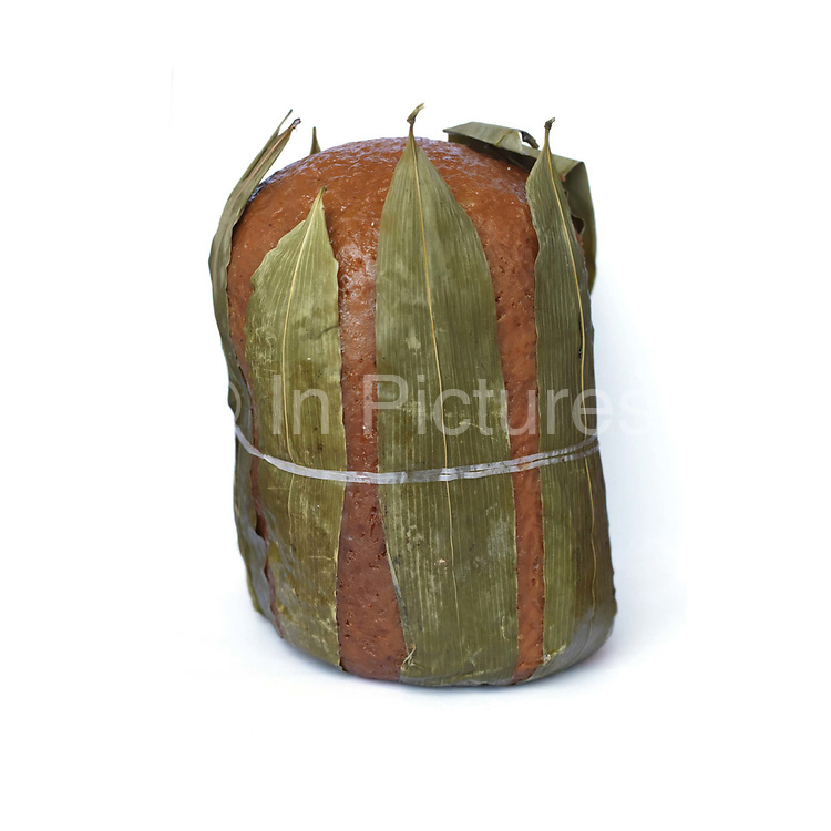 A large sticky rice cake wrapped in leaves from Sa La Xi village market; Guizhou province, China.