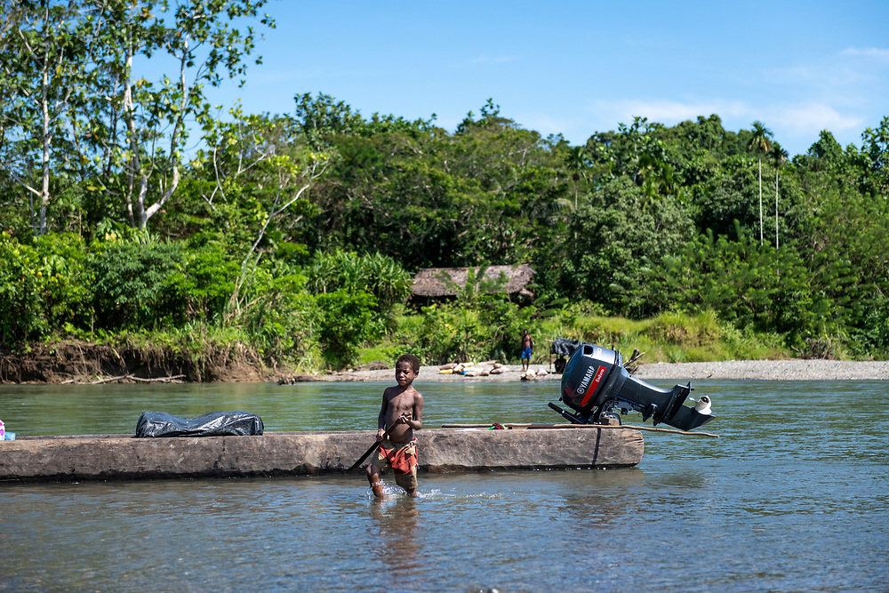 A boy walks with a machete in the Clay River in Likan, East Sepik Province, Papua New Guinea.
