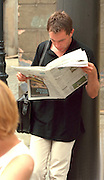 Man age 25 leaning against pole reading newspaper intensely.  Poznan Poland