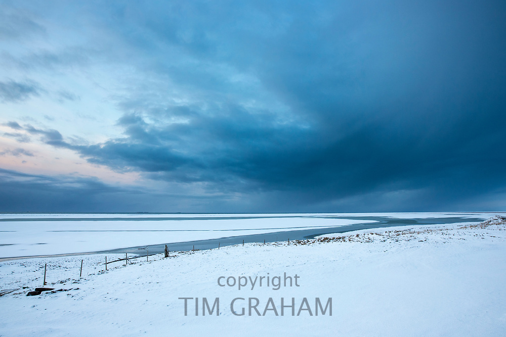 Wintry sun and puffy clouds above typical Icelandic snow-covered plains landscape towards the Atlantic Ocean near Hofn, South Iceland