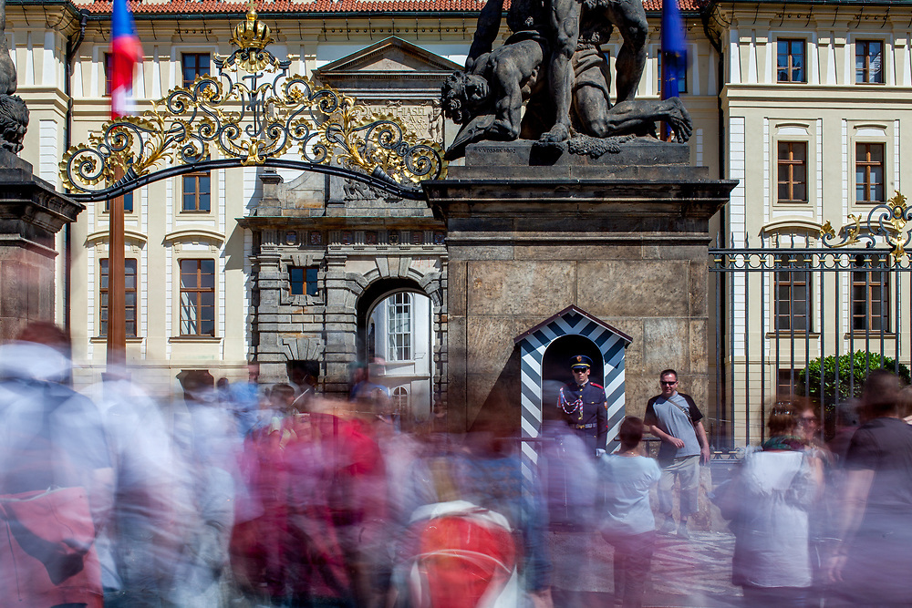 """Visitor getting their portraits taken with the Prague Castle Guards in-front of the Wrestling Titans (Sousoší Souboj Titánů), also known as Fighting Giants and Giants' Gate, which are pair of outdoor sculptures leading to the first courtyard of Prague Castle at """"Hradcany Square"""" (Hradcanske Namesti)."""