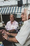 Gjirokastër, Albania - September 11, 2013: Albanian men seen through the window of a cafe in Gjirokastër, Albania.