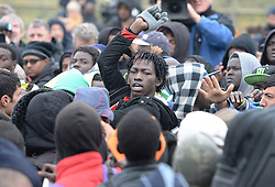 """Tempers flair up among a large crowd of migrants as they line-up at a processing centre in """"the jungle"""" near Calais, northern France, as the mass exodus from the migrant camp begins."""