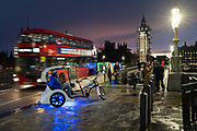 Rickshaw drivers await new business opposite the Houses of Parliament on Westminster Bridge, during the second lockdown of the UK Coronavirus pandemic, on 15th November 2020, in London, England. Rickshaws with modified motors count as motor vehicles requiring drivers have a driving licence and insurance and can be seized by police.