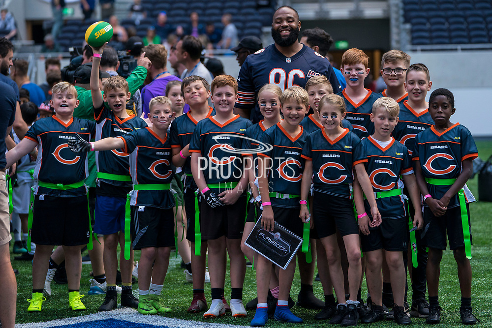 Akeem Hicks (DT, Chicago Bears) poses the kids ahead of todays NFL Flag National Championship Finals during the NFL UK Media Day at Tottenham Hotspur Stadium, London, United Kingdom on 3 July 2019.