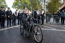 London, UK. 13 October, 2019. A disabled climate activist from Extinction Rebellion protests outside New Scotland Yard against tactics employed by police officers which impinge on the right to protest of disabled activists, including the confiscation of wheelchairs, wheelchair ramps, accessible toilets and tents. It was the seventh day of International Rebellion protests by Extinction Rebellion.
