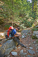 Hiker stops to read a topo map on the Pine Ridge Trail, Big Sur, California.