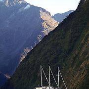 A Real Journey's tourist cruise ship dwarfed by the steep cliff faces of Milford Sound, South Island, New Zealand. .Milford Sound (Piopiotahi in Ma¯ori) is a fjord in the south west of New Zealand's South Island, within Fiordland National Park and the Te Wahipounamu World Heritage site. It has been judged the world's top travel destination and is acclaimed as New Zealand's most famous tourist destination..Milford Sound runs 15 kilometres inland from the Tasman Sea at Dale Point - the mouth of the fiord - and is surrounded by sheer rock faces that rise 1,200metres (3,900ft) or more on either side. Among the peaks are The Elephant at 1,517metres (4,977ft), said to resemble an elephant's head and The Lion, 1,302metres (4,272ft), in the shape of a crouching lion. Lush rain forests cling precariously to these cliffs, while seals, penguins, and dolphins frequent the waters and whales can be seen sometimes..Milford Sound sports two permanent waterfalls all year round, Lady Bowen Falls and Stirling Falls. After heavy rain many hundreds of temporary waterfalls can be seen running down the steep sided rock faces. .The beauty of this landscape draws thousands of visitors each day, with between 550,000 and 1 million visitors in total per year. This makes the sound one of New Zealand's most-visited tourist spots, and also the most famous New Zealand tourist destination.  Milford Sound, New Zealand. 30th April 2011. Photo Tim Clayton