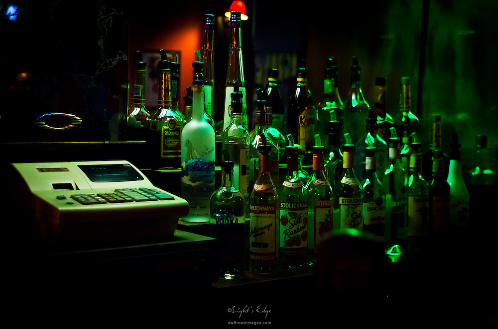 Bottles of the basic booze for a corner bar sit in the lime light.