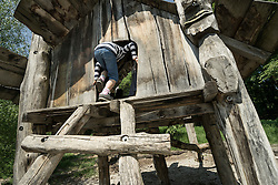 Rear view of girl playing on tree house in playground, Munich, Bavaria, Germany