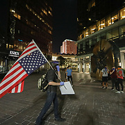 CHARLOTTE, NC - June 2: A man with an upsidedown flag walks near the corner of Trade and Tryon Street in uptown Charlotte, NC on June 2, 2020. The days long protest in cities around the world was sparked by the police killing of George Floyd by Minneapolis PD officer,  Derek Chauvin while 3 officers watched.  (Photo by Logan Cyrus for AFP)