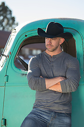 cowboy leaning against a vintage truck