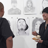 042215      Cayla Nimmo<br /> <br /> Benny Cross, left, and Julyan Sanderson, right, art students at University of New Mexico's Gallup Campus, enjoy food and looking at the work of fellow students at the gallery opening Wednesday night. The show features work from photography, ceramics, and drawing students and is open to the public in UNM-G's Gurley Hall.