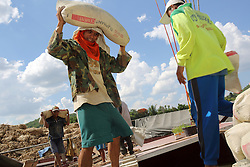 Labourers work to unload a Cargo river boat carrying cement on the River Mekong in the early morning.  Luang Prabang port, Luang Prabang Province, Lao PDR