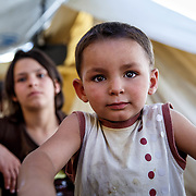 Muhamed, 3, with his sister, Fatimah, 13, from Aleppo, Syria. Ritsona Refugee Camp, Greece, July 2016.
