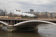 Steam train crossing the railway bridge across the River Thames at Battersea on 7th April 2018 in London, England, United Kingdom. lThe locomotive is the UKs youngest steam engine, the 60163 Tornado.
