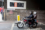 Motorcycle with a pillion passenger passes the On Your Bike sign on Stainer Street, London.