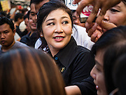 11 NOVEMBER 2016 - BANGKOK, THAILAND:  YINGLUCK SHINAWATRA looks over her shoulder while greeting supporters at a rice distribution sale in the Bangkok suburbs. Yingluck was deposed in a coup in 2014, has started selling rice directly to Thai consumers. She buys the rice from farmers at market prices and then sells it to urban consumers at the price she paid. She said she's doing it to help out farmers, who are trying to deal with depressed prices. Yingluck is facing prosecution on corruption related charges going back to a rice price support scheme her government used to try to help farmers in 2011 and 2012. Even after the coup, she is still personally popular and hundreds of people showed up to see her at the rice distribution point at a mall in Samut Prakan province, in suburban Bangkok.  PHOTO BY JACK KURTZ