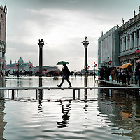 A tourists walks on one of the temporary wooden walkways near Palazzo Ducal on St Mark Square.An extreme high tide of around 145 cm above sea level has hit Venice today San Marco is one of the six sestieri of Venice, lying in the heart of the city.