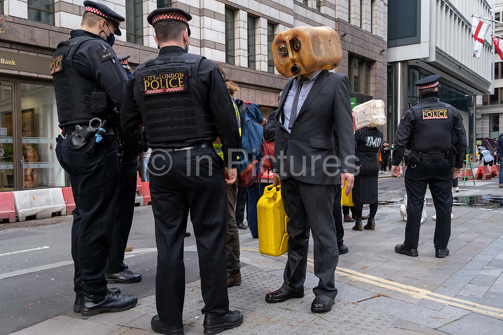 Extinction Rebellion Climate Change activists dressed in City suits, vomit 'oil' outside the Baltic Exchange, home to the International Chamber of Shipping (ICS) who, according to environmentalists, are co-sponsoring the IMO's non-regulation, thereby allowing fossil fuel emissions by the shipping industry, on 16th November 2020, in London, England. 'Scrubbers' then appeared to metaphorically clean-up the mess left on the pavement before City of London Police officers arrived to re-open the street during this, the second lockdown during the Coronavirus pandemic