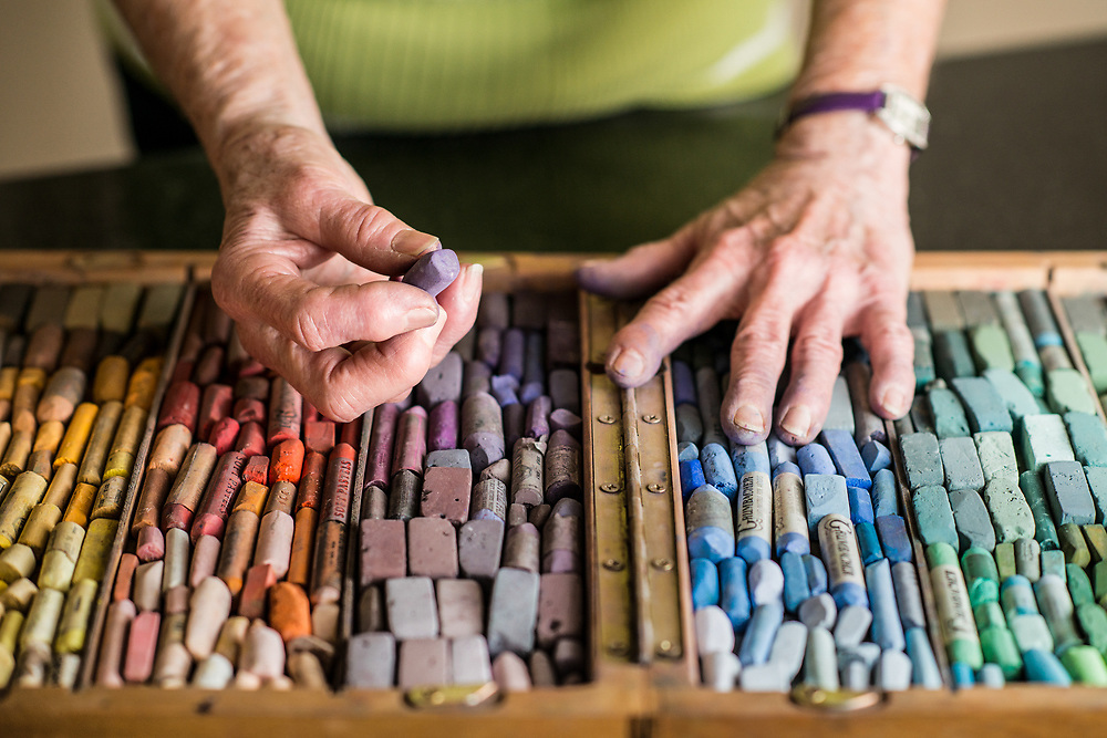 Mary Anne Stafford, Arkansas artist and educator, holds her most cherished medium, a colorful set of oil pastels. This image was created by Arkansas based commercial photographer, Alex Kent