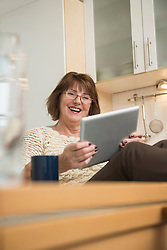 Senior woman using a digital tablet and smiling in the kitchen, Munich, Bavaria, Germany