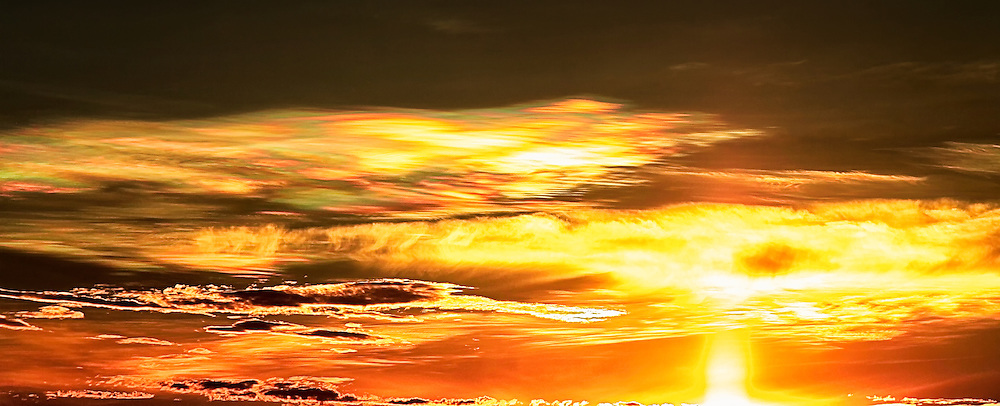 The Play of Light: Sunrise creates a predominantly golden, surrealistic scene as light parts the sky on the horizon and refracted light creates an array of colours that are cast throughout the clouds, over Battamgbang Cambodia.