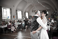 Bride and groom dancing first dance while guests watch