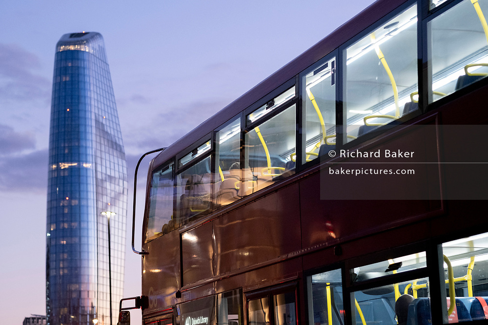 Seen from the City of London, One Blackfriars (one of the capital's newest skyscrapers) rises above a London bus during the evening rush-hour, on 26th February 2021, in London, England. Located on Bankside, the south bank of the river Thames, the development is a 52-storey 170m tower whose uses include residential flats, a hotel and retail.