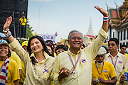 05 MAY 2104 - BANGKOK, THAILAND:  SUTHEP THAUGSUBAN (right) and his wife, SRISAKUL PROMPHAN (left) lead a march of anti-government protesters to Sanam Luang in Bangkok. Thousands of Thais packed the area around Sanam Luang and the Grand Palace Monday evening for a special ceremony to mark Coronation Day, which honored the 64th anniversary of the coronation of Bhumibol Adulyadej, the King of Thailand. Many of the people also support the anti-government movement led by Suthep Thaugsuban. Most of the anti-government protesters are conservative supporters of the monarchy.   PHOTO BY JACK KURTZ