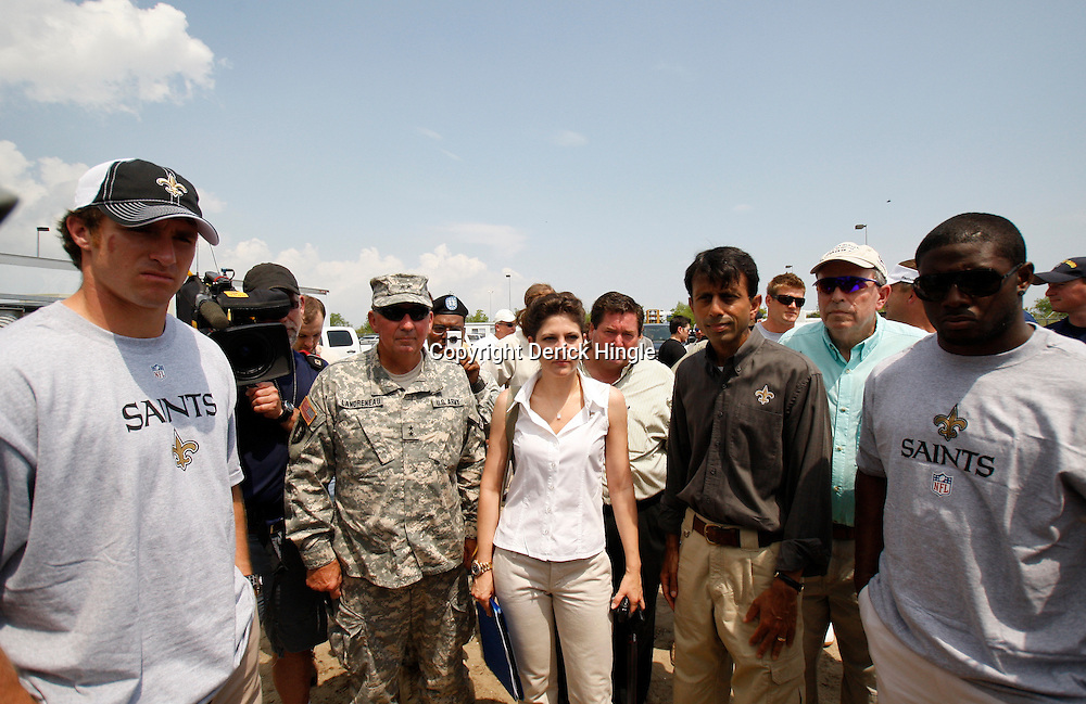 June 8, 2010; Buras, LA, USA; New Orleans Saints quarterback Drew Brees (left) along with teammate running back Reggie Bush (right) and Louisiana Governor Bobby Jindal (second to right) get a safety briefing prior to seeing pelicans cleaned in a bird rehab center at Fort Jackson. The entire team held a rally at Fort Jackson and visited with members of the small Plaquemines Parish fishing community of Buras that has been impacted by the oil spill. Mandatory Credit: Derick E. Hingle-US PRESSWIRE