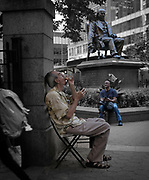 Two self-occupied people sit in a park adjacent to a sitting statue as a passer-by hurries past.