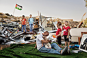Khalid Zir and his five daughters take a break beside the ruins of their demolished home, in the East Jerusalem neighborhood of Silwan.