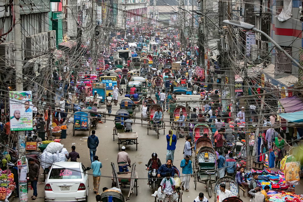 INDIVIDUAL(S) PHOTOGRAPHED: N/A. LOCATION: Dhaka, Bangladesh. CAPTION: Power lines zigzag and crisscross the view of a busy street filled with market stalls, cars, rickshaws, pedestrians and motorcycles in Dhaka.