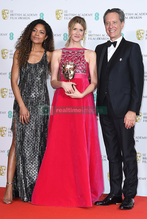Naomie Harris and Richard E Grant pose for a photo with Laura Dern and her award for Best Supporting Actress at the 73rd British Academy Film Awards held at the Royal Albert Hall, London.. Photo credit should read: Doug Peters/EMPICS