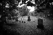 Backlite black and white of headstones with dramatic lighting. Black & White from RAW