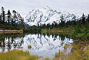 A snowy Mount Shuksan (9127 feet elevation), located in North Cascades National Park, reflects in Picture Lake, in Heather Meadows, in Mount Baker - Snoqualmie National Forest, Washington.