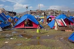 26/11/2013.  A young boy walks past a row of tents which are now home to residents of the city of Tacloban more than 2 weeks after a super typhoon destroyed the city in the Phiippines.  Photo credit: Alison Baskerville/LNP